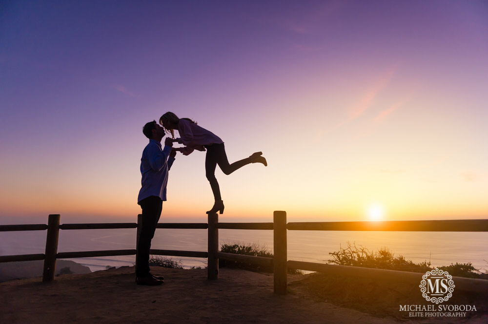 A silhouette of a couple kissing at sunset at Torrey Pines State park.  The women is balancing on the wooden fence while the man helps her balance.