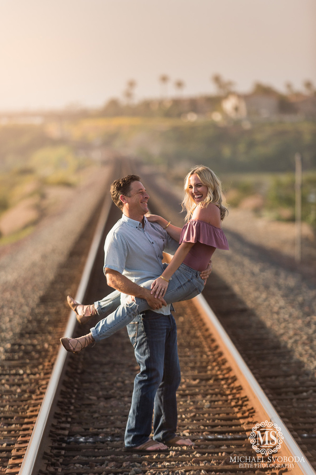 A loving couple standing on railroad tracks.  The women is straddling hime laughing.