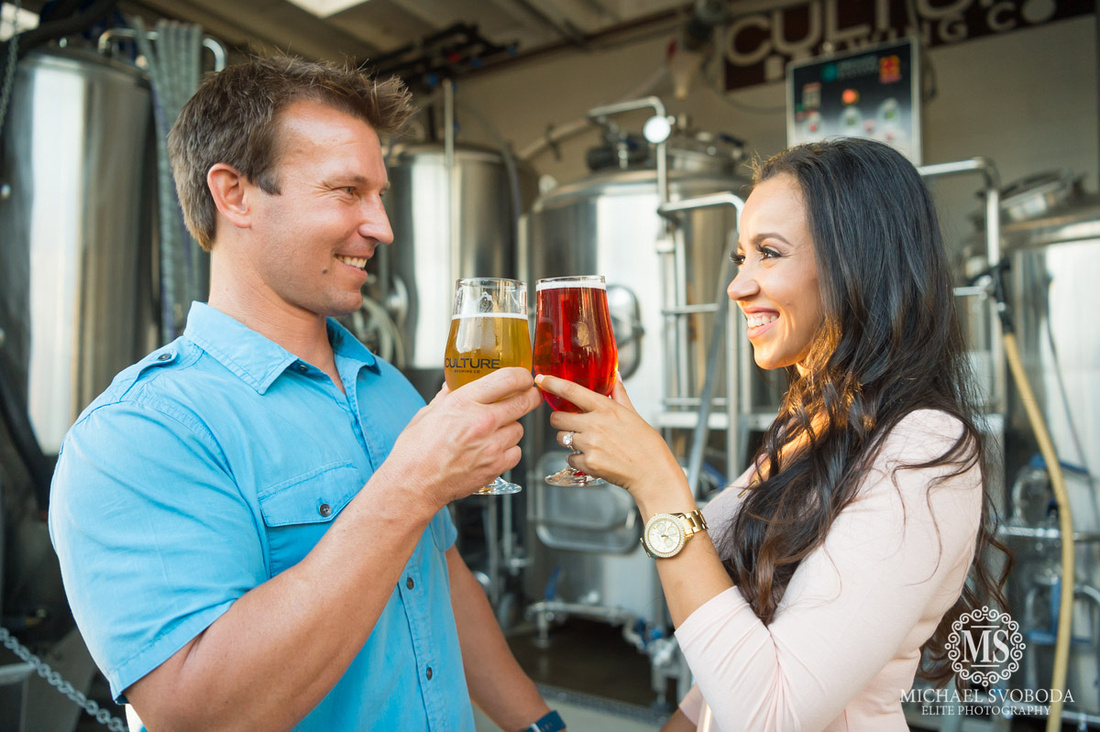 A ggod looking couple cheers ing their beers at a brewery looking into each others eyes.