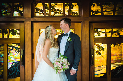 Bride and groom looking into each others eyes in front of beautiful yellow back lit stained glass.