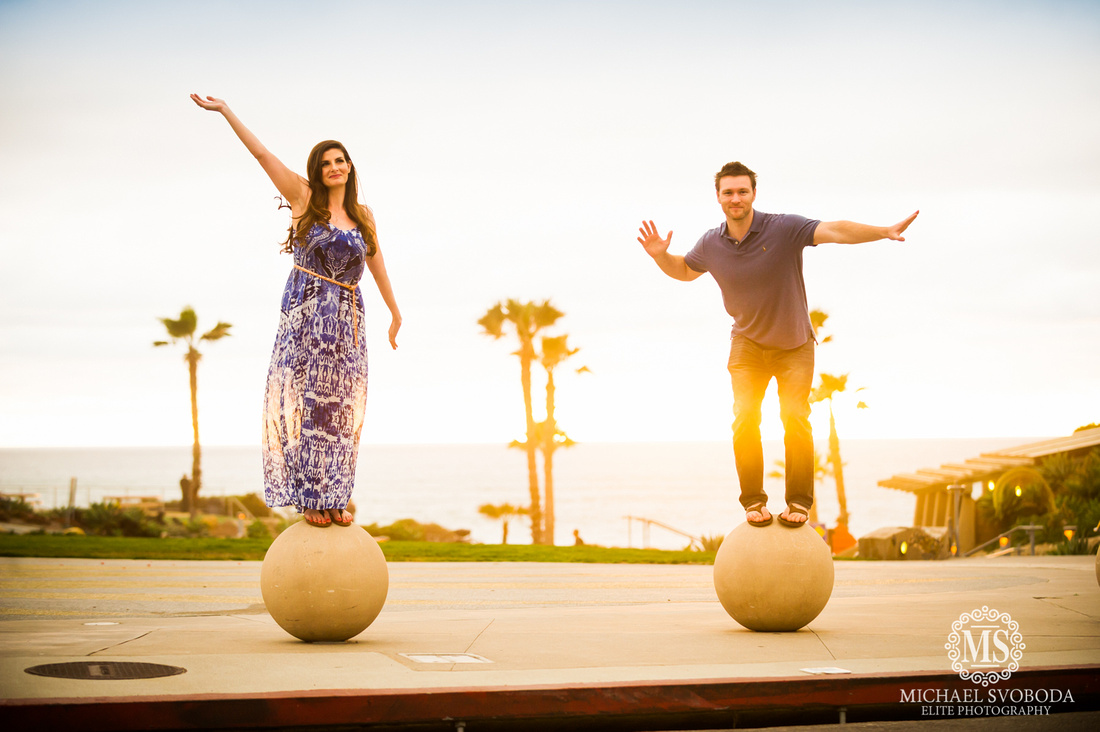A couple balancing on two stone balls with the ocean behind.