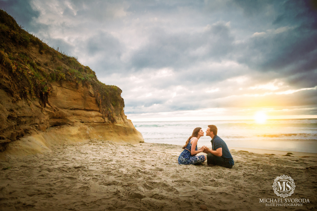 A romantic couple sitting in the sand going in for the kiss while the sunsets behind the ocean's horizon.