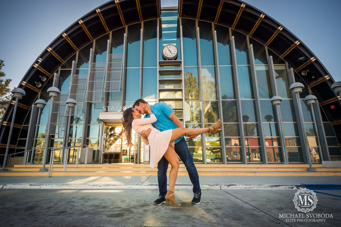 A couple dipping and kissing in front of a domed like building.
