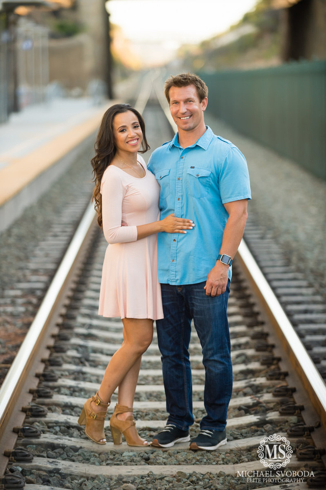 A cute couple standing on the railroad tracks smiling for the camera.